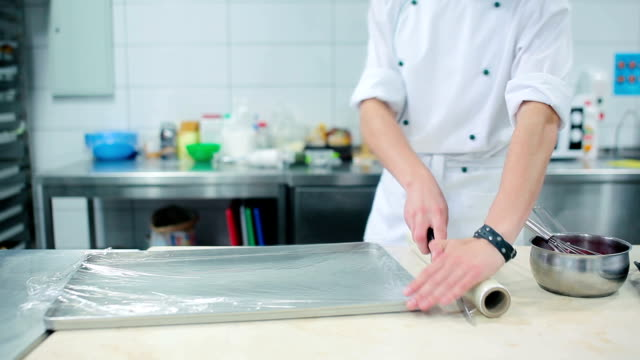 Man unwinds plastic wrap over the baking. video