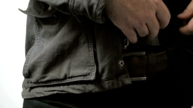 Man Unzips Jacket and Pulls Handgun Out of Pants in Slow Motion video