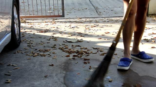man use broom sweeping fallen leaves video