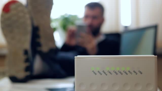 一名男子在辦公室裡使用智慧手機, 雙腿折疊在桌子上。無線路由器。中拍攝 - 無線技術 個影片檔及 b 捲影像