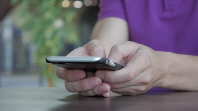 man använder en smartphone för att skriva ett meddelande i ett café - telefonmeddelande bildbanksvideor och videomaterial från bakom kulisserna