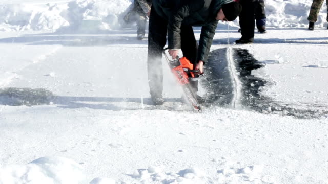 a man uses a special saw to cut the ice for extreme sailing on the frozen lake on a snowy - monti urali video stock e b–roll
