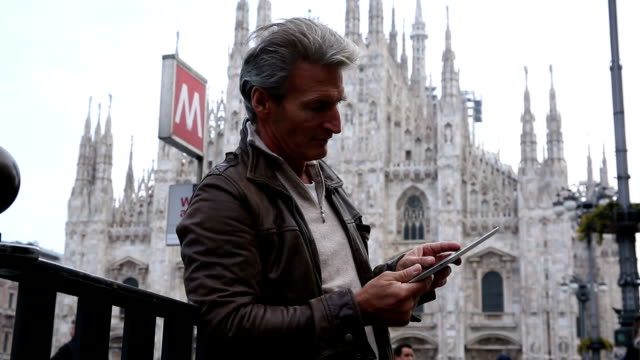 Man uses digital tablet, in front of Duomo, Milan, Italy video