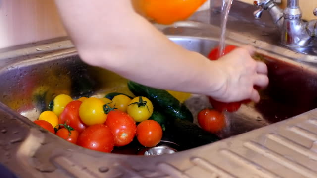 Man uses hands, running water, to sweep vegetable waste down grinding, kitchen sink garbage disposal. 1080p HD video