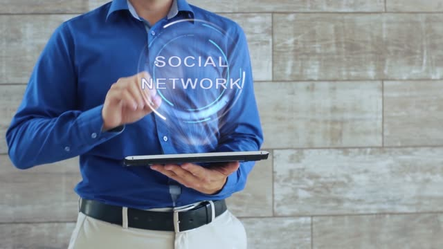 Man uses hologram with text Social network Man activates a conceptual hologram with text Social network. The guy in the blue shirt and light trousers with a holographic screen gadget on the background of the wall multimedia stock videos & royalty-free footage