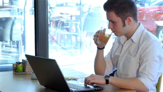 vídeos y material grabado en eventos de stock de un hombre utiliza un ordenador portátil en el café - vibrisas