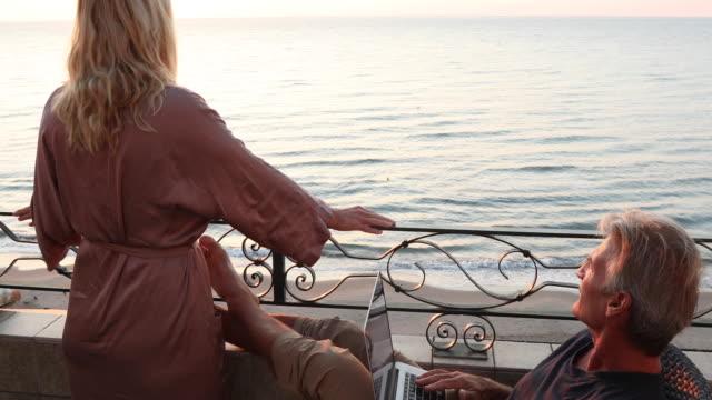 Man uses laptop computer at sunrise, above sea