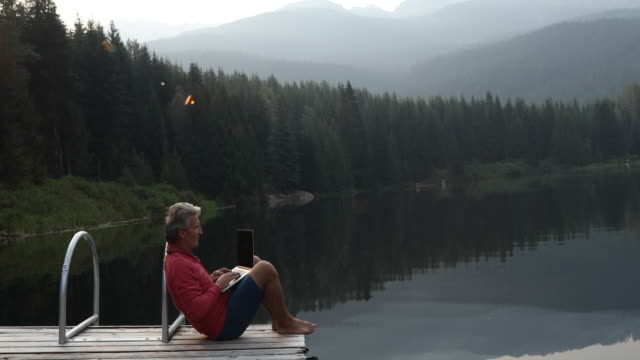 man uses laptop computer while sitting on pier at sunrise - molo video stock e b–roll