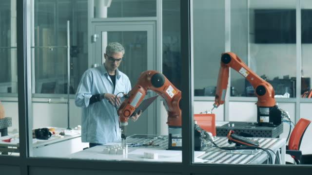 vídeos de stock e filmes b-roll de a man uses laptop to control robotic arm. modern science laboratory. - braço