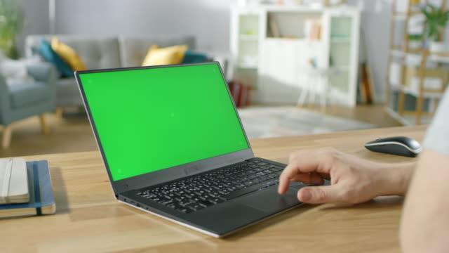 mann nutzt laptop mit grünen mock-up bildschirm sitzend am schreibtisch in seinem gemütlichen wohnzimmer. - laptop stock-videos und b-roll-filmmaterial