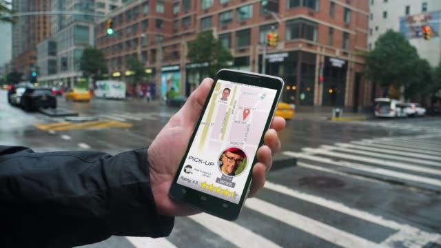 man uses ride sharing app on phone to call driver - położenie filmów i materiałów b-roll