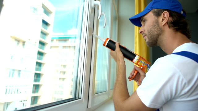 vídeos de stock e filmes b-roll de man uses silicone adhesive with glue gun to repair worn window, sound insulation - isolador