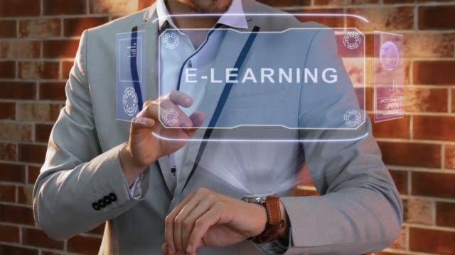 vidéos et rushes de l'homme utilise l'hologramme de montre intelligente e-learning - étudiant(e)