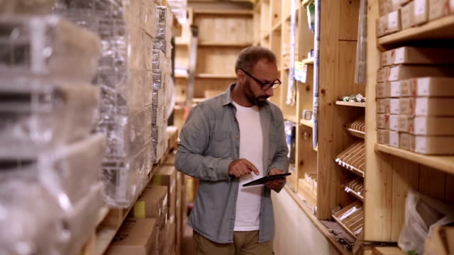 Man uses the digital tablet to control in the warehouse Man uses the digital tablet to control in the warehouse storage room stock videos & royalty-free footage