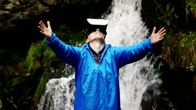 A man uses virtual reality glasses on the background of a mountain waterfall video