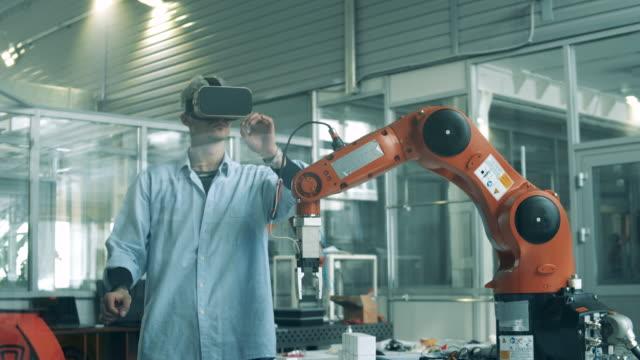 vídeos de stock e filmes b-roll de man uses vr glasses to control robotic arm at factory. - membro