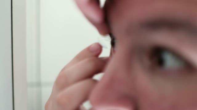 vídeos de stock e filmes b-roll de man using a contact lens - contacts