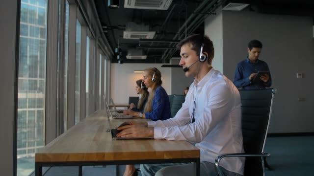 mann mit einem kopfhörer während der arbeit im callcenter büro - reliability stock-videos und b-roll-filmmaterial