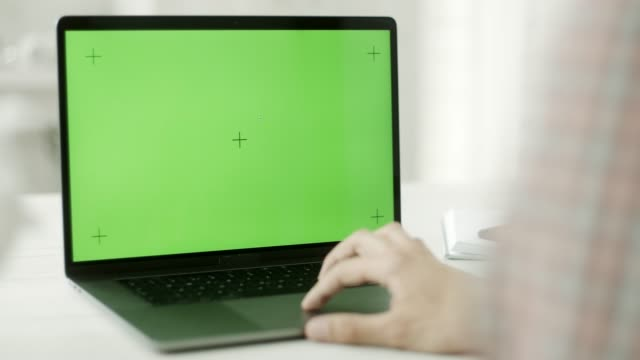 A man using a laptop with a green screen