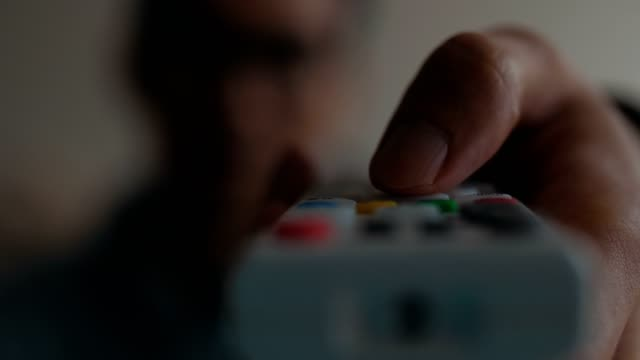 man using a remote control watching tv