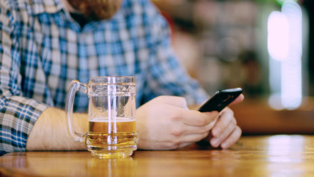 DS CU Man using a smart phone while drinking a beer video