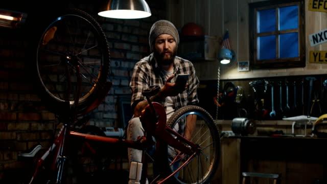 mann mit einem smartphone in einer werkstatt - garage stock-videos und b-roll-filmmaterial