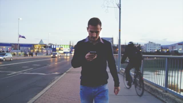 ws-man använder en smartphone medan promenader på trottoaren - bekymmerslös bildbanksvideor och videomaterial från bakom kulisserna