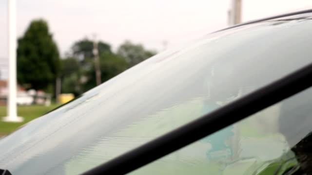 vidéos et rushes de homme à l'aide d'une raclette en caoutchouc sur son pare-brise dans une station-service - raclette
