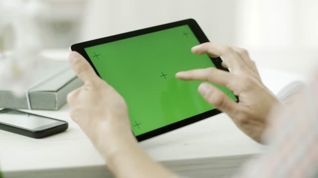 ein mann mit einem tablet mit einem green-screen - schriftrolle stock-videos und b-roll-filmmaterial