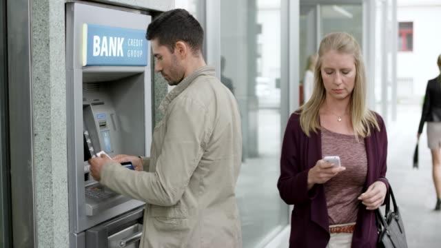 man använder en bankomat på en upptagen gata för att göra ett uttag - blazer bildbanksvideor och videomaterial från bakom kulisserna