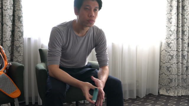 Man using asthma inhaler at home to prevent his chronic illness video