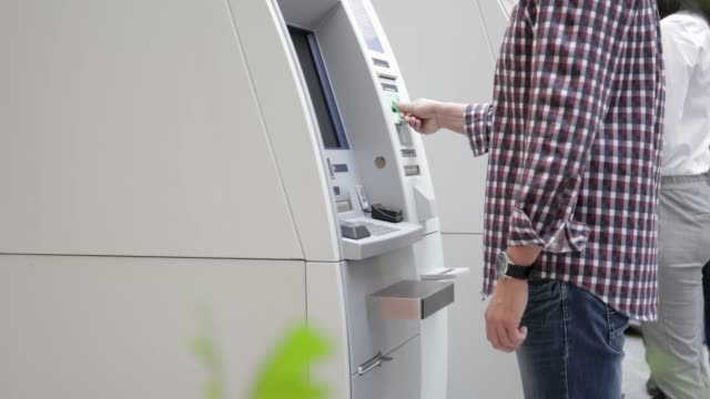 man using atm, handheld shot - banks and atms stock videos & royalty-free footage