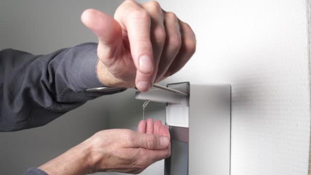 vídeos y material grabado en eventos de stock de hombre usando dispensador automático de desinfectante de manos - hand sanitizer