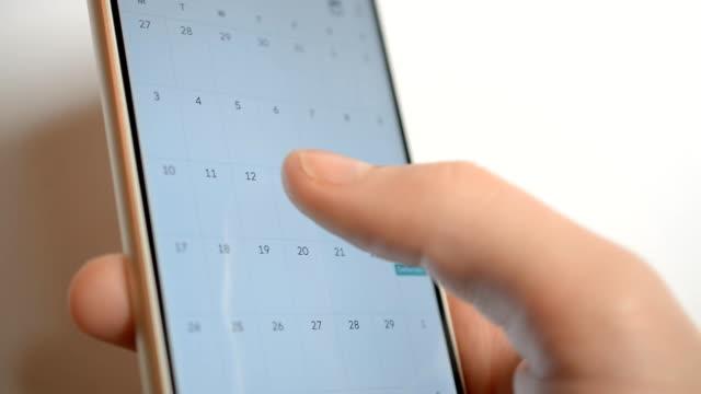 vídeos de stock, filmes e b-roll de homem que usa o app do calendário no closeup do dispositivo móvel - calendário