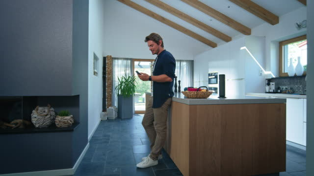 Man using cellphone while entering kitchen