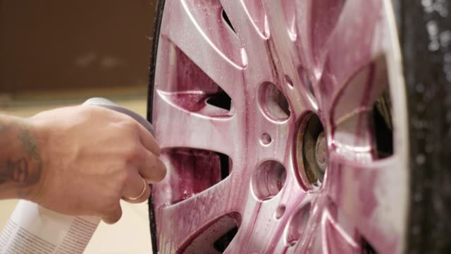 Man using chemistry for cleaning sport car wheel, slow motion video