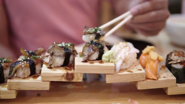 A man using chopsticks for eating Fresh sashimi in a japanese restaurant.