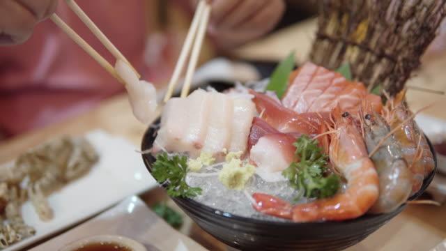 Man using chopsticks for eating Fresh sashimi in a japanese restaurant.