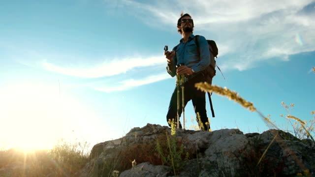 Man using compass on mountain