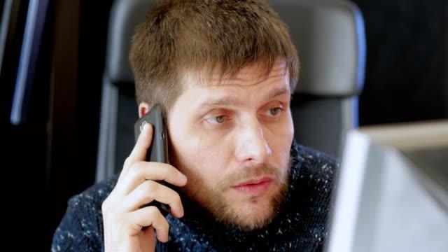 vidéos et rushes de homme utilisant l'ordinateur et parlant sur le téléphone portable. - un seul homme d'âge mûr