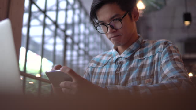 man using computer in cafe - cultura orientale video stock e b–roll