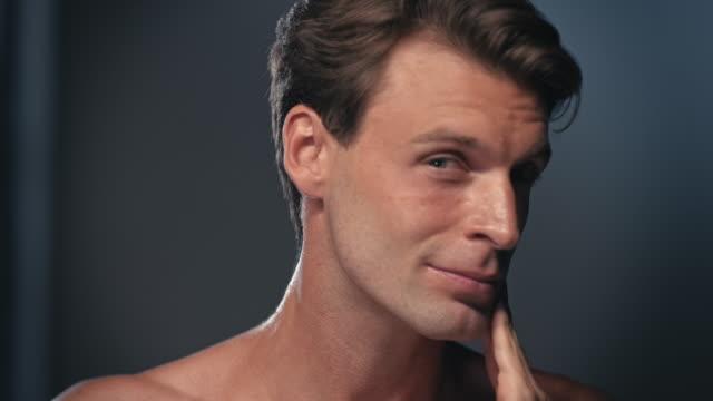 彼の顔にクリームを使用している人 - 体 洗う点の映像素材/bロール