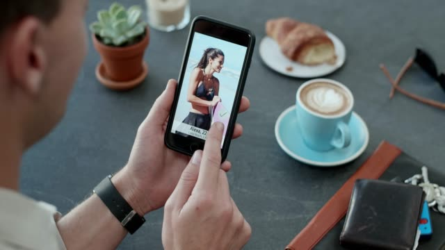 man using dating social app, finding romance love connection caucasian man finding connection with other singles on dating app while at cafe drinking coffee romance stock videos & royalty-free footage