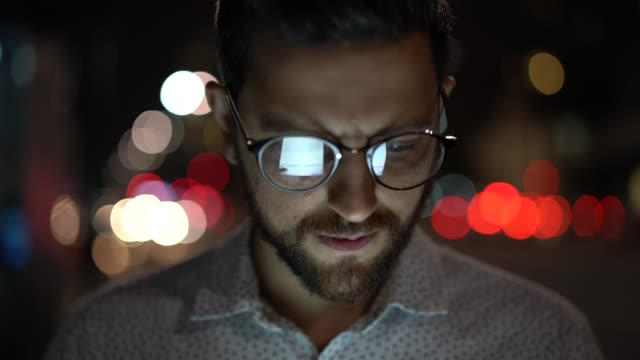 밤에 디지털 태블릿을 사용 하는 남자 - 헌신 스톡 비디오 및 b-롤 화면