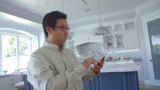 uomo utilizzando compressa digitale di controllo l'illuminazione a casa - cultura coreana video stock e b–roll