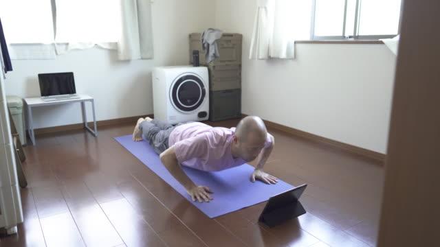 自宅で腕立て伏せのために訓練するためにデジタルタブレットを使用して男 - 体への関心点の映像素材/bロール