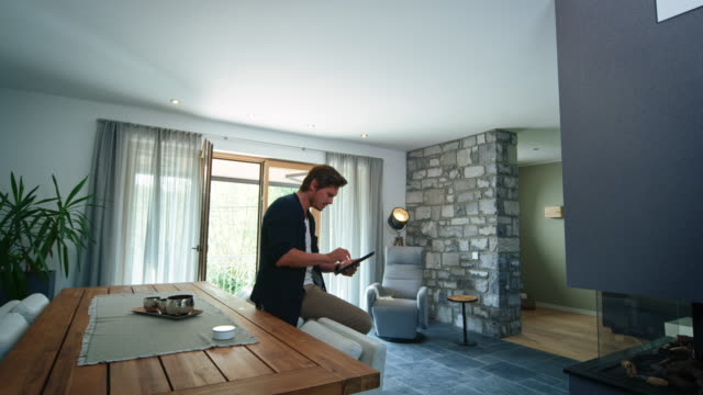 의자에 앉아있는 동안 디지털 태블릿을 사용하는 남자 - 가정의 방 스톡 비디오 및 b-롤 화면