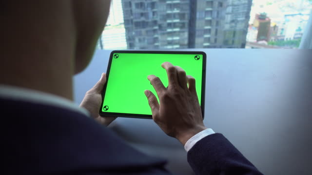 Man using Digital Tablet with green screen hold in hands