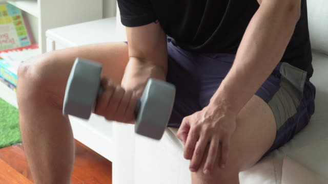 Man using dumbbell doing workout at home