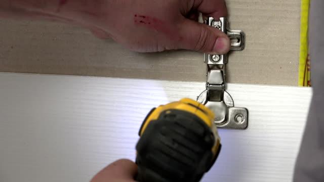 Man using electric screwdriver to tighten screw on kitchen door hinge video